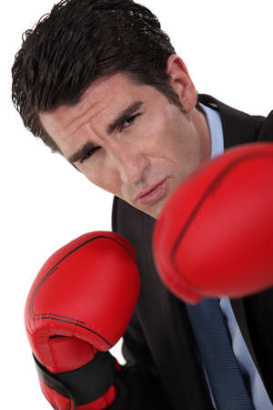 Businessman wearing boxing gloves photo