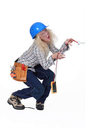 multimeter: Electrocuted tradeswoman holding a multitester
