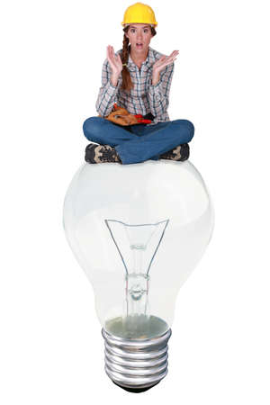 Woman with expression of surprise sat on a big light bulb photo