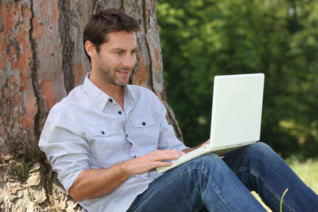 chemise: Man sat by tree with laptop