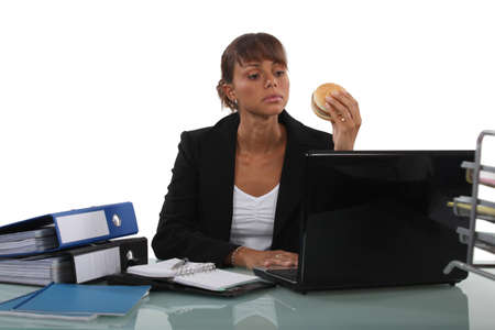rushed: Woman eating a  burger at her desk Stock Photo