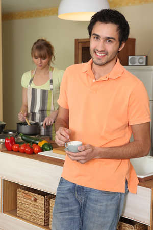 stirring: Young woman stirring into saucepan and man holding cup of coffee