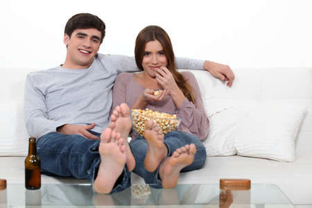 Young couple on a sofa watching a movie photo