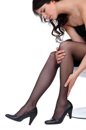 Woman in heels rubbing her calf Stock Photo - 13645640