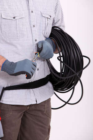 interconnect: Man preparing length of wire