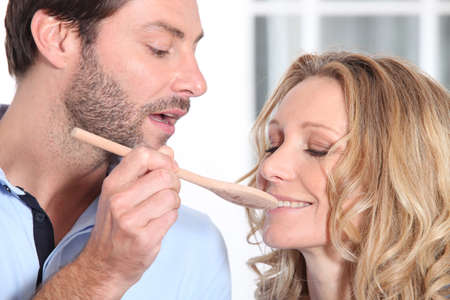 man having her wife taste preparation photo