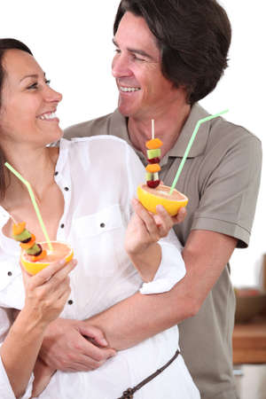 Couple in kitchen holding dessert photo