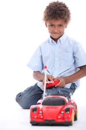 little boy playing with a toy car photo