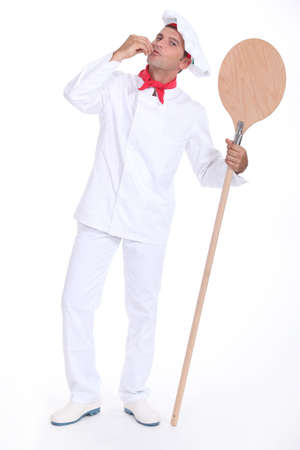 Pizza chef holding a pizza loading peel photo
