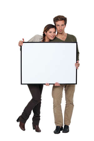 Trendy young couple stood with blank frame photo