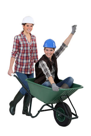 barrow: craftswoman carrying a colleague sitting in a wheelbarrow Stock Photo