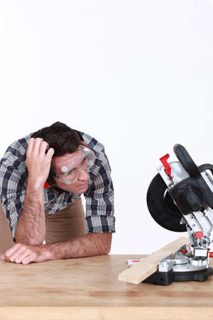 A perplexed carpenter looking at a circular saw  photo
