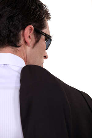 cosa: Mobster carrying his jacket over his shoulder