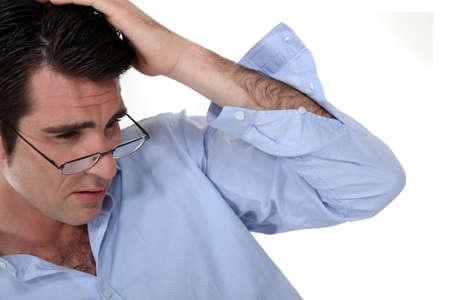 difficult task: Businessman rubbing his head