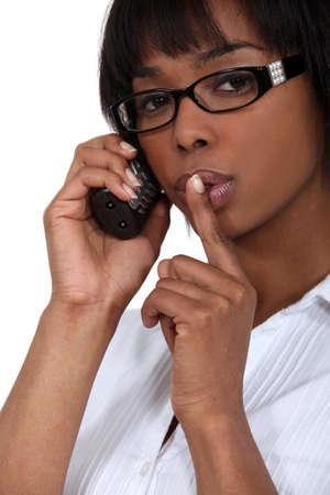 shush: Woman making shush gesture whilst using telephone