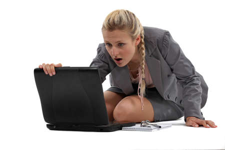 bending over: blonde open-mouthed in surprise before laptop Stock Photo