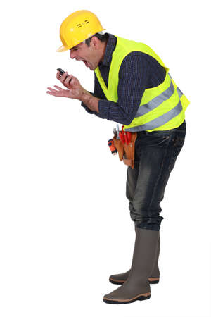 business disagreement: foreman screaming in a mobile phone Stock Photo