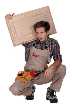 hunker: portrait of young cabinetmaker carrying cupboard door over shoulder