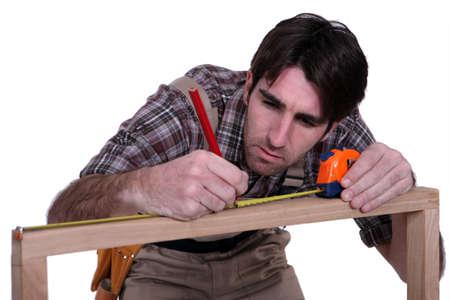 trussing: L'uomo misura telaio in legno Archivio Fotografico