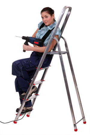 Woman with drill sitting on metal staircase Stock Photo - 13713682