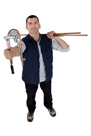 fittings: Man using copper pipe bending tool