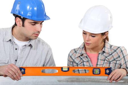 female apprentice and carpenter using ruler photo