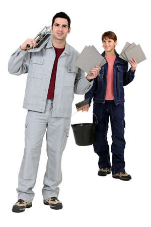 workwoman: Tile fitters holding up their building supplies and tools