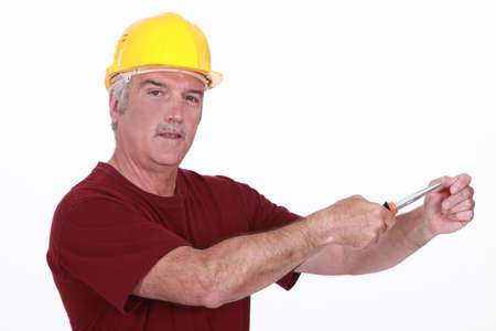 grey haired: Grey haired man using screw driver