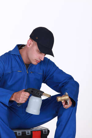 Plumber using blow torch on brass pipe photo