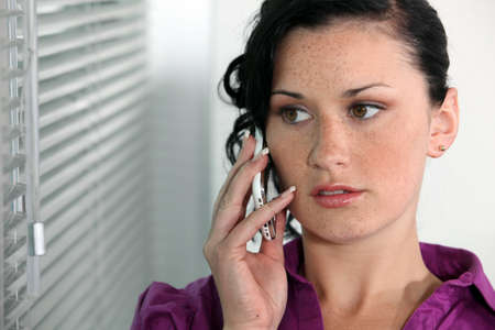 unemotional: Attractive young woman talking on her mobile phone