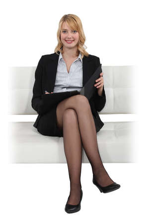 controling: young businesswoman on a sofa Stock Photo