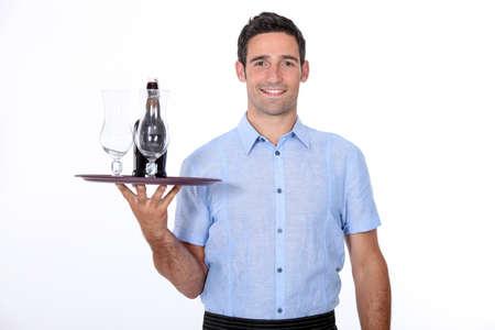 A waiter bringing a bottle of liquor  photo