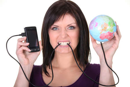 Woman frustrated at her phone plugged into a globe photo