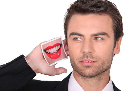 a business man with a mouth picture near his ear photo