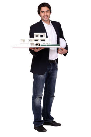architect holding a helmet and a model of a house Stock Photo - 13713735