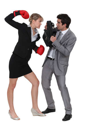 businesswoman threatening male colleague with boxing gloves photo