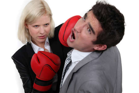 businesswoman hitting a colleague with a boxing glove photo