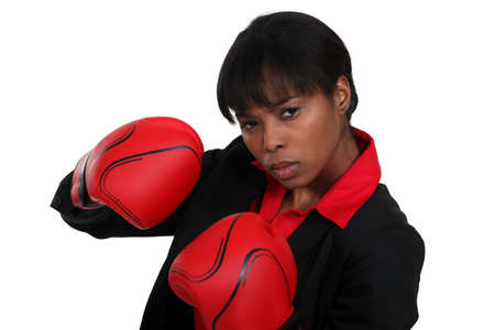 Female office worker wearing boxing gloves photo