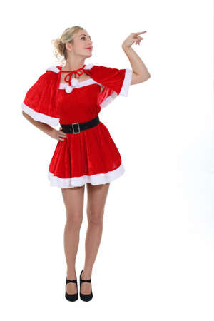 santa helper: gorgeous blonde in christmas outfit pointing to her side