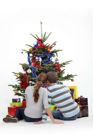 Couple sitting in front of a Christmas tree photo