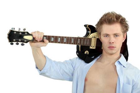 nackte brust: Ernsthafter junger Mann mit seiner Gitarre über die Schulter Lizenzfreie Bilder