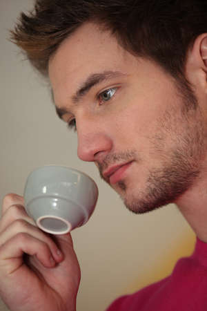 A pensive man drinking a cup of coffee photo