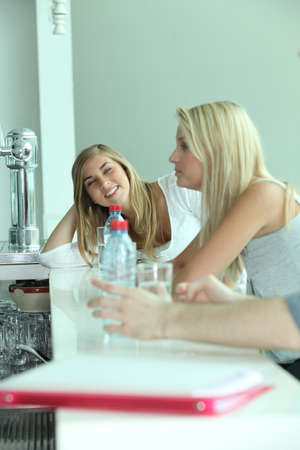 Young girls drinking bottled water in a bar photo
