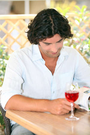 Man reading with a glass of rose in the sunshine photo