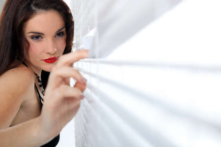 Sexy woman peeking through some blinds photo