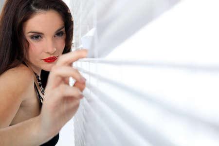 Sexy woman peeking through some blinds photo