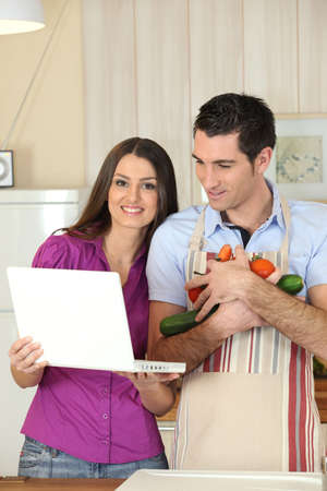 Couple looking-up recipe on laptop photo