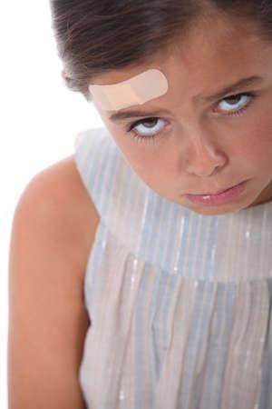petite fille triste: Fille avec une blessure sur le front