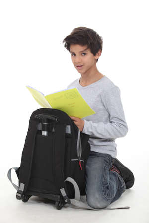 knelt: Schoolboy kneeling by backpack Stock Photo