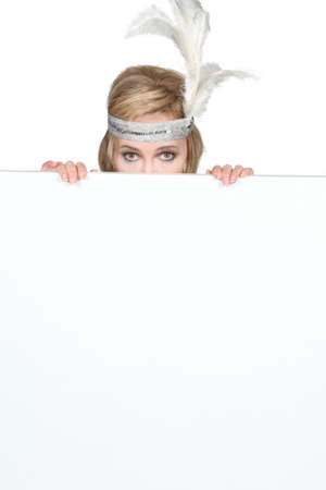 Woman wearing a feathery headpiece hiding behind a blank sign photo
